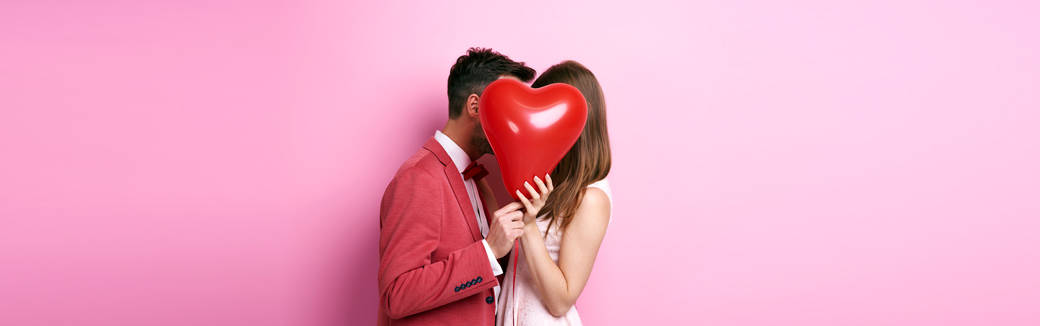 couple kissing behind a heart-shaped balloon
