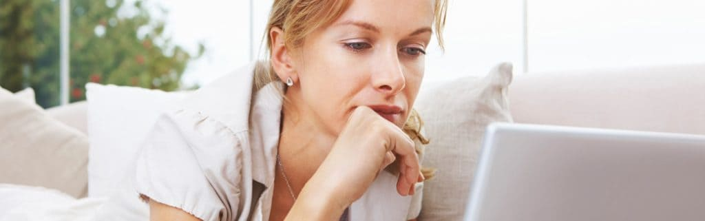 woman with her chin in her hand looking at her computer.
