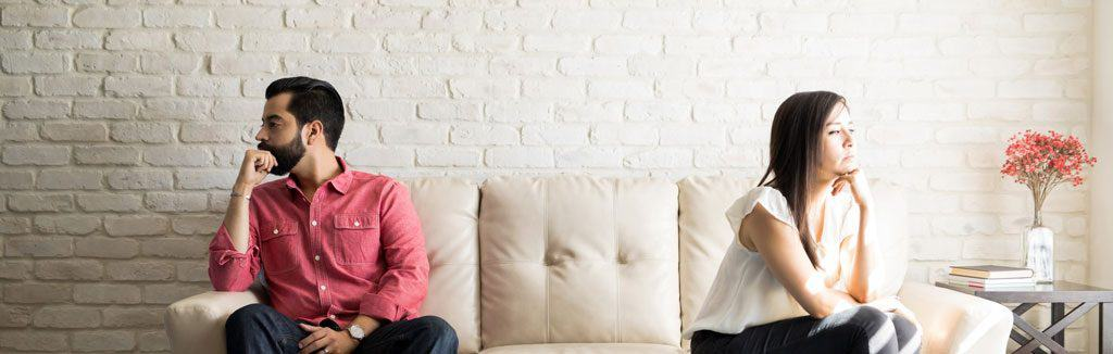 man and woman sitting on opposite ends of the couch, facing away from each other.