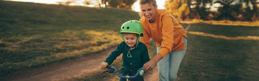 mom helping child to ride a bike