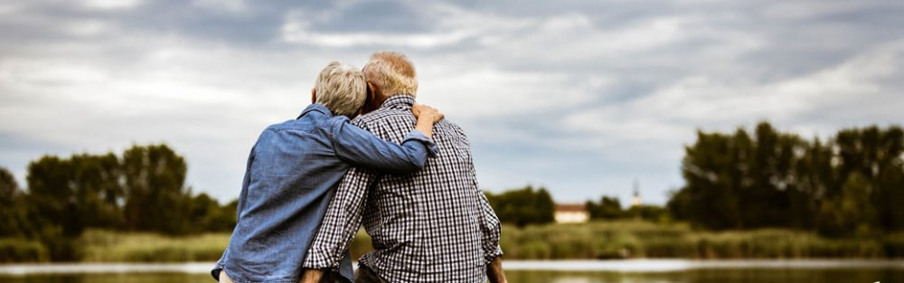 older couple outside with their back to us, arms around each other